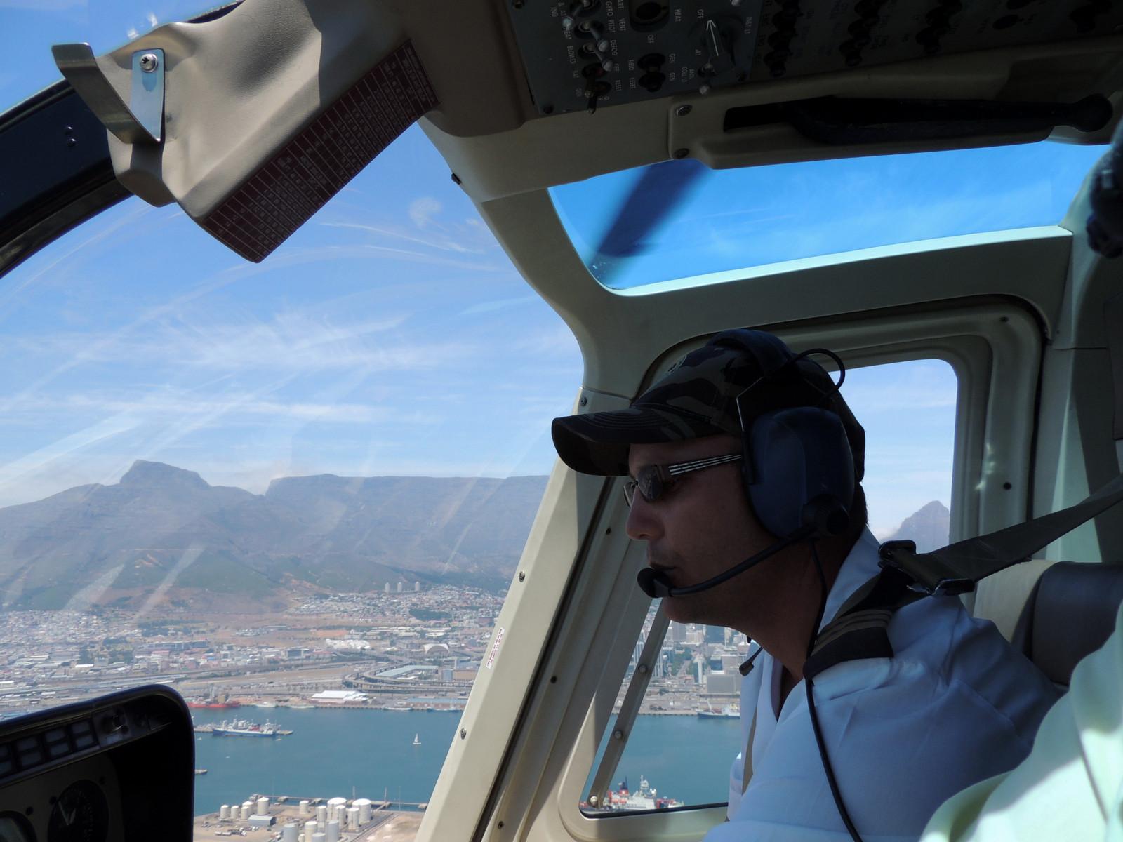Hubschrauberpilot vor dem Tafelberg in Kapstadt